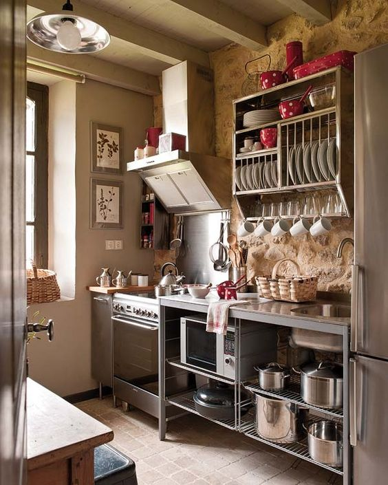 a vintage industrial kitchen with free-standing metal cabinets and much open shelving looks airy