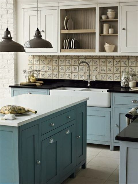 freestanding blue kitchen cabinets with black and white countertops create an elegant feel, and vintage touches add more chic