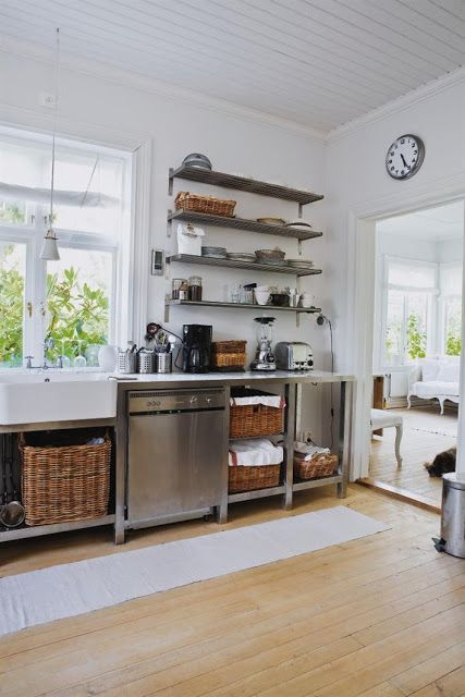 metal cabinets on legs with much open shelving and baskets for storage that soften the look