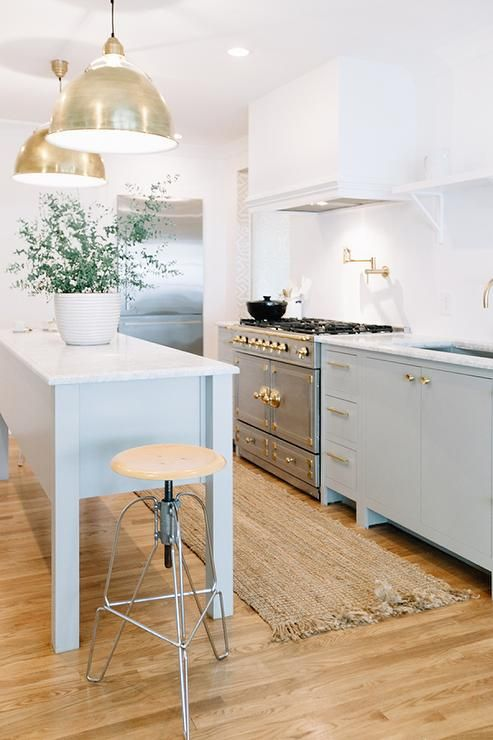 pastel freestanding kitchen cabinets with brass touches and a kitchen island on tall legs for a