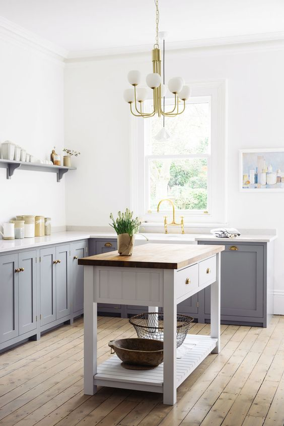 vintage-inspired grey freestanding cabinets with white marble countertops for a peaceful and welcoming kitchen
