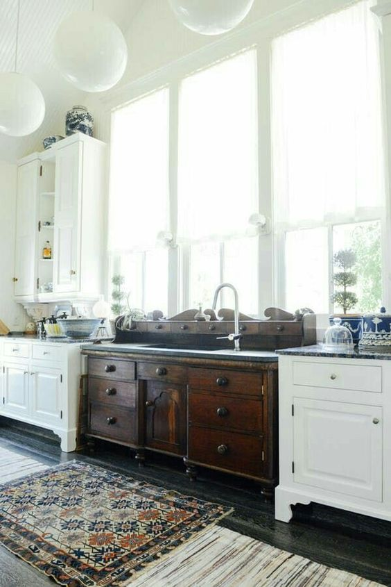 vintage white and dark wood cabinets on legs are used for an eclectic and catchy kitchen look