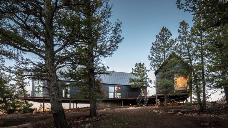 This rustic cabin duo is located on a remote site in the forest and features minimal impact on the nature