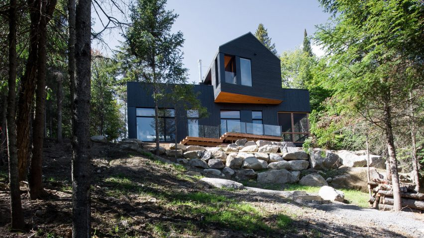 This unique black chalet is located in the forest and has views of the lake, it's built for siblings who have separate but intersecting home parts