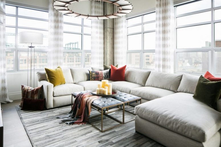 Large windows bring much light inside, and a large corner sofa with a double upholstered bench creates a cozy space