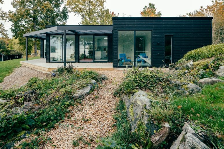 The house features dark exterior to blend with the surroundings and much glazing to enjoy the views