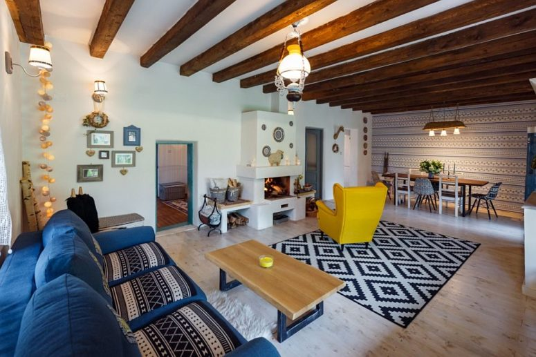 The living room and dining space are united into one layout, with wooden beams and colorful furniture