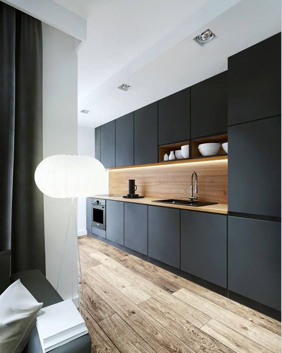 a black kitchen is made more interesting with a light-colored wood backsplash and an aged wood floor