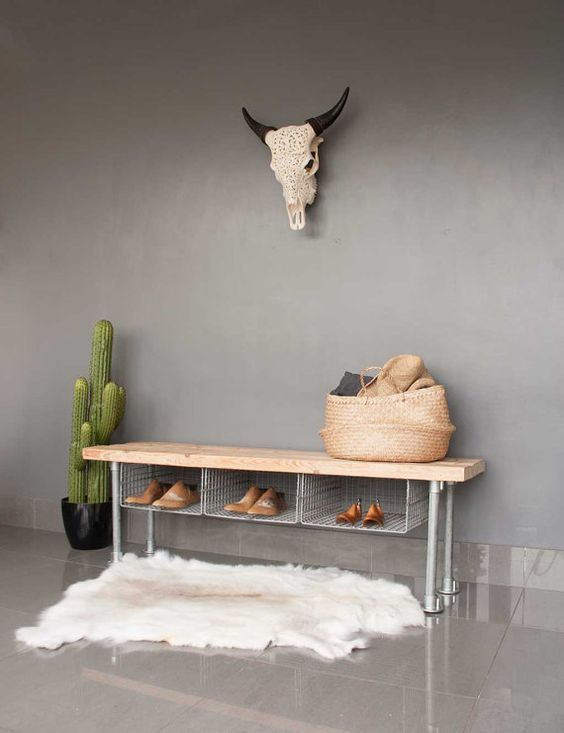 a metal shoe rack bench with wire storage compartments and a wooden top for an industrial space