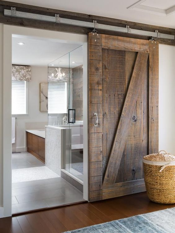 a modern space features sliding barn doors of reclaimed wood that make a bold rustic statement