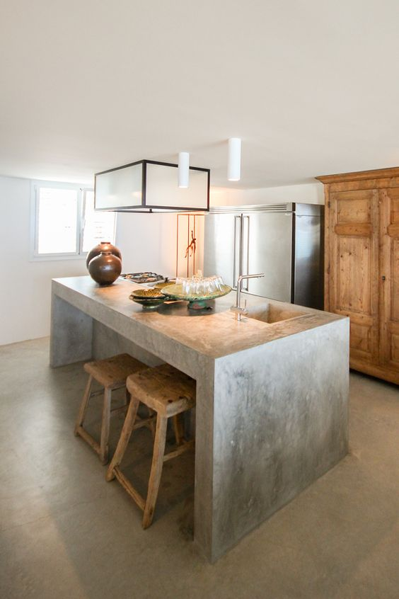 a simple concrete kitchen island with a breakfast space is also an industrial idea but brings a modern vibe