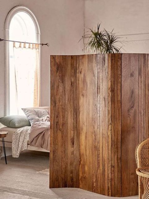 a stained reclaimed wooden screens is a cool idea to separate a studio apartment