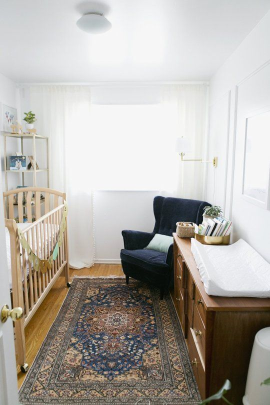 a white nursery is filled with a navy velvet chair, a printed rug and a brown wooden dresser