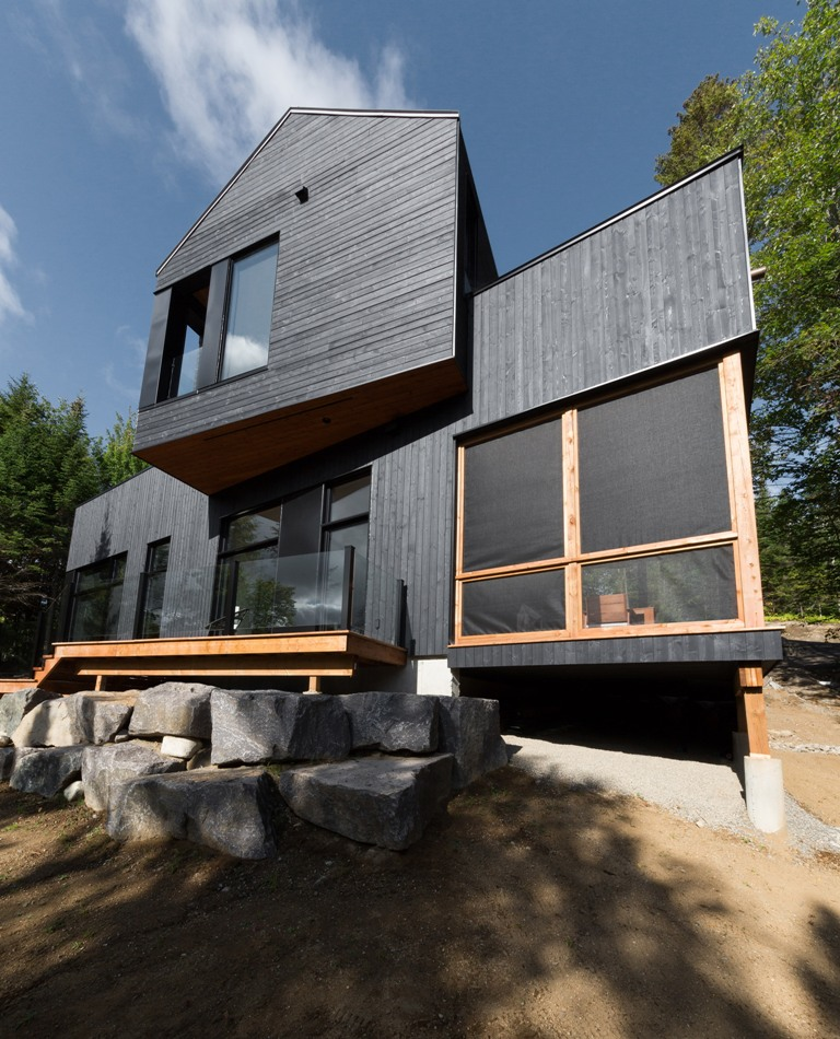 The house features extensive glazings to catch the views of the lake and forests