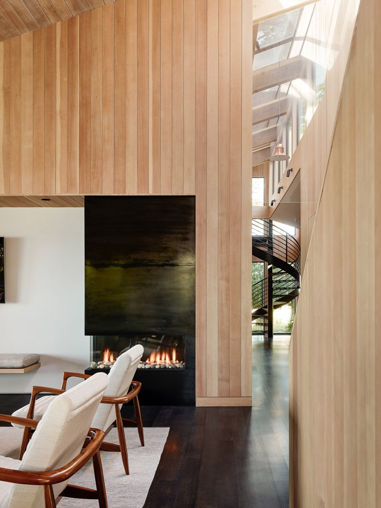 The inside of the home is clad with the same light colored wood as outside, and the color palette is comfortable and earthy