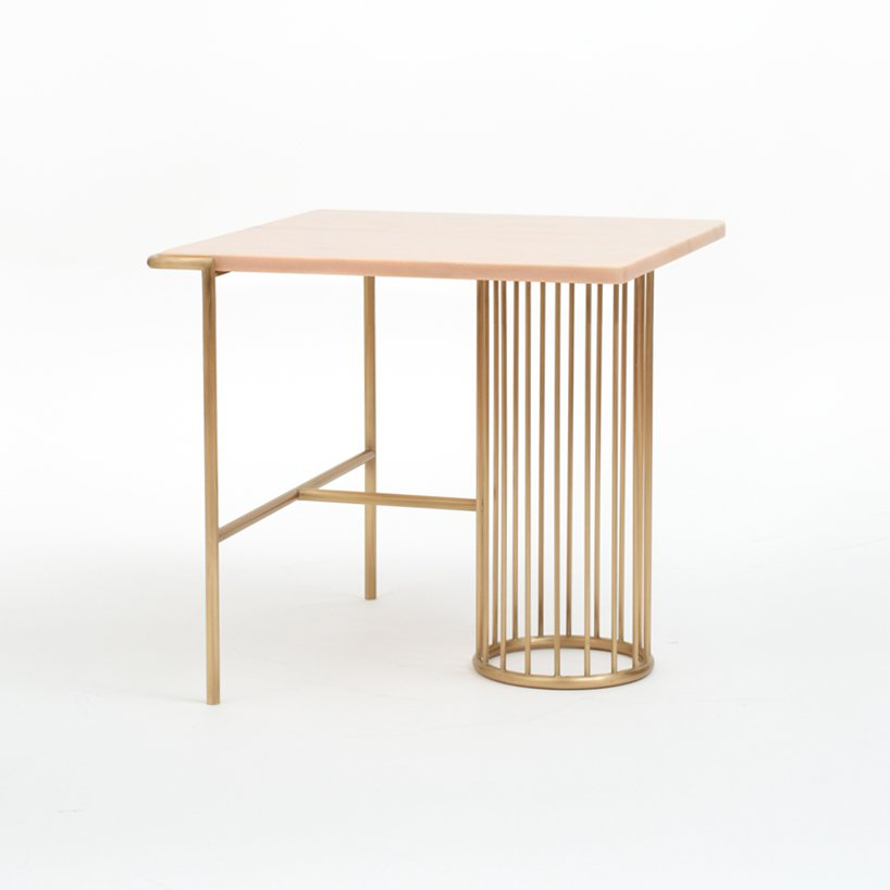 The side table is made of brass and pink marble, which is a stylish and sophisticated combo