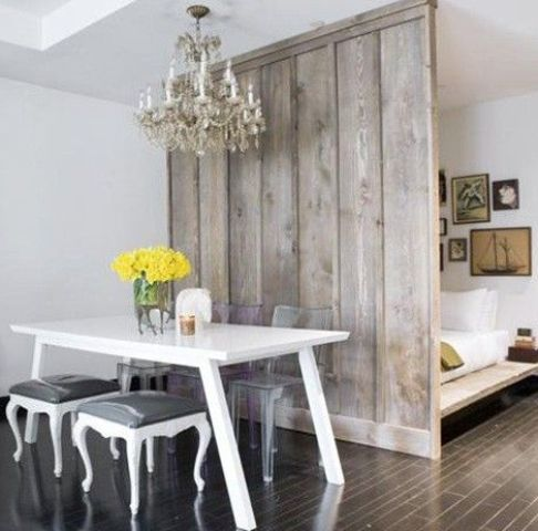 a rustic grey wooden screen makes the sleeping space more private and adds coziness to the shabby chic space