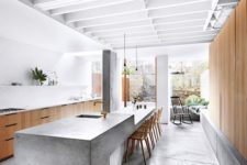 03 a sculptural and long concrete kitchen island features a dining space on one end