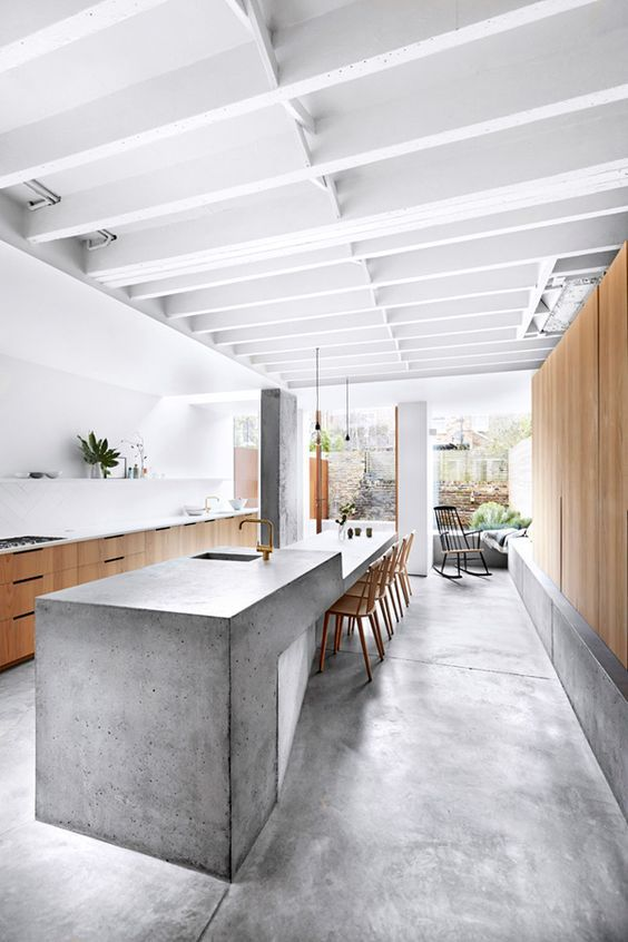 a sculptural and long concrete kitchen island features a dining space on one end
