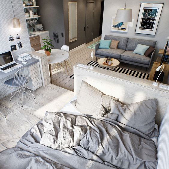 a small studio apartment done in the shades of grey and off-white for a modern feel