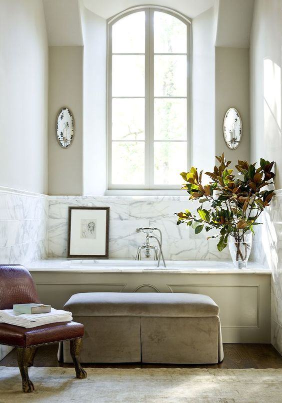 a vintage space with a bathtub clad with marble and the walls around it clad with the same for a refined feel
