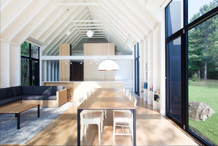The dining space shows off a simple minimalist dining table and white chairs next to the glazed wall