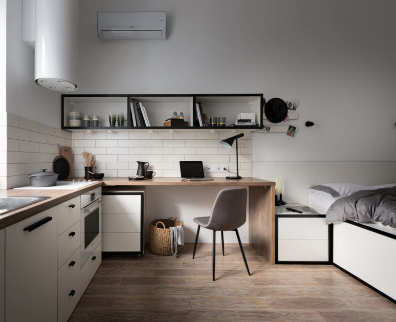 The furniture is modern and simple, there's a built in cooker, a modern hood with lights and much storage