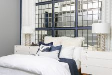 04 The guest bedroom is more glam, with exposed pipes, a concrete ceiling and a framed mirror headboard wall