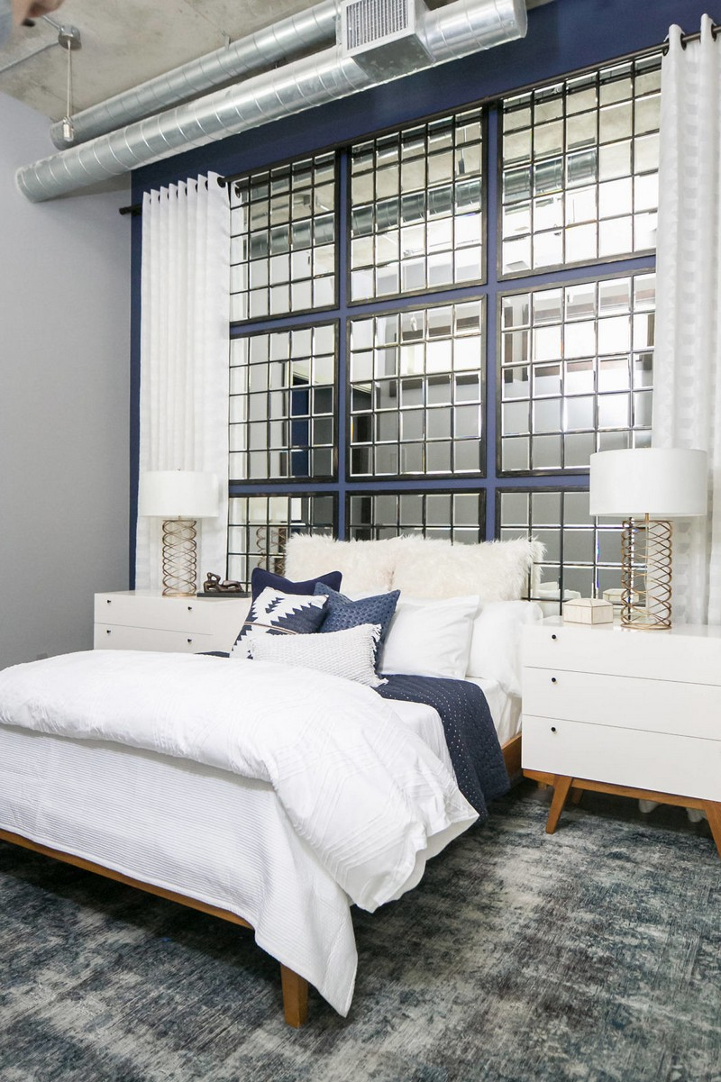 The guest bedroom is more glam, with exposed pipes, a concrete ceiling and a framed mirror headboard wall