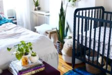 04 a boho shared master bedroom with a nursery nook with a navy crib and baskets for storage