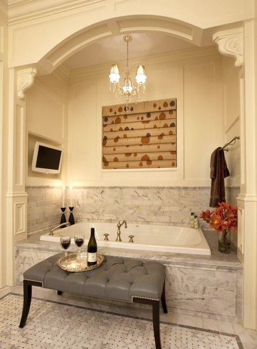 a chic and romantic niche with a bathtub clad with grey marble tiles and a backsplash covered with them, too