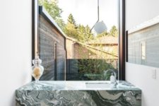 04 a green marble modern vanity in a small powder room with a view to the courtyard