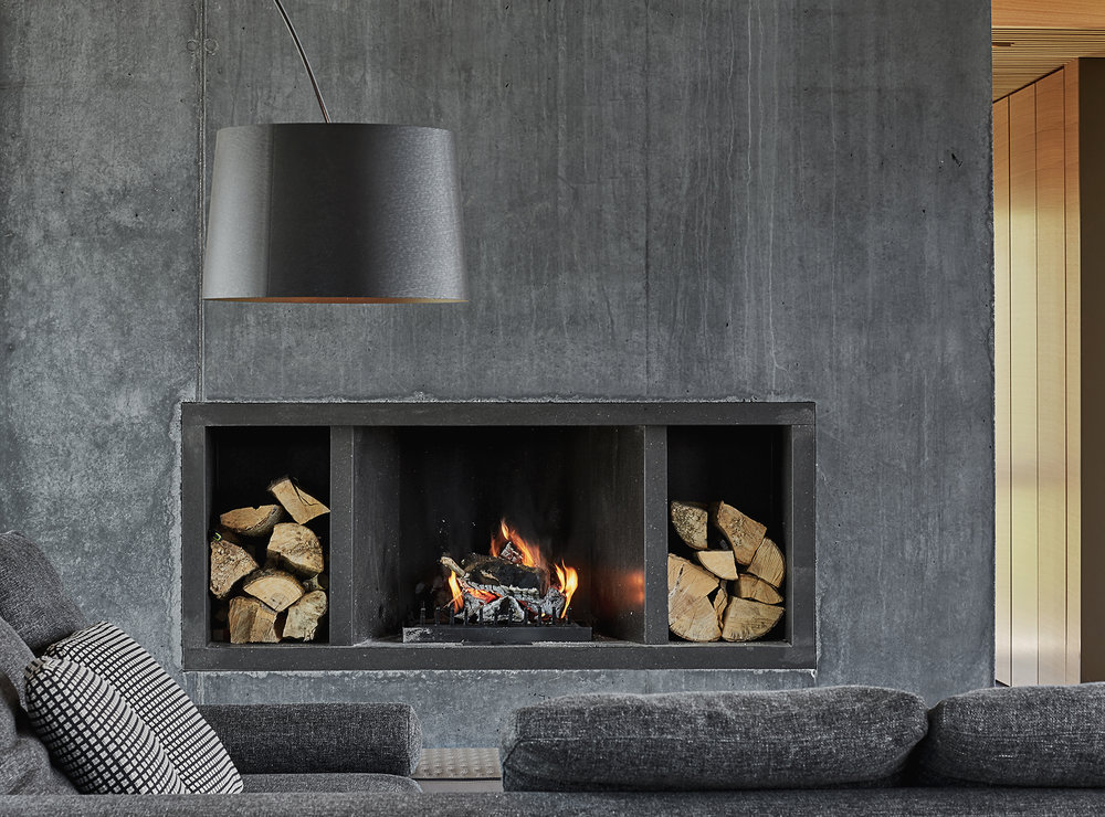 Here you may see a concrete built in fireplace with firewood storage and comfy grey felt furniture