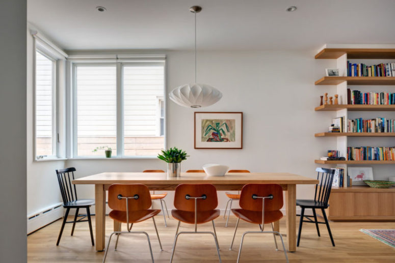 The dining space features a wooden table and orange wooden chairs