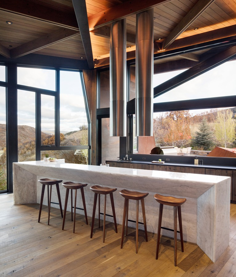 The kitchen features full glazing to catch the views, a stone kitchen island and a modern tube hood