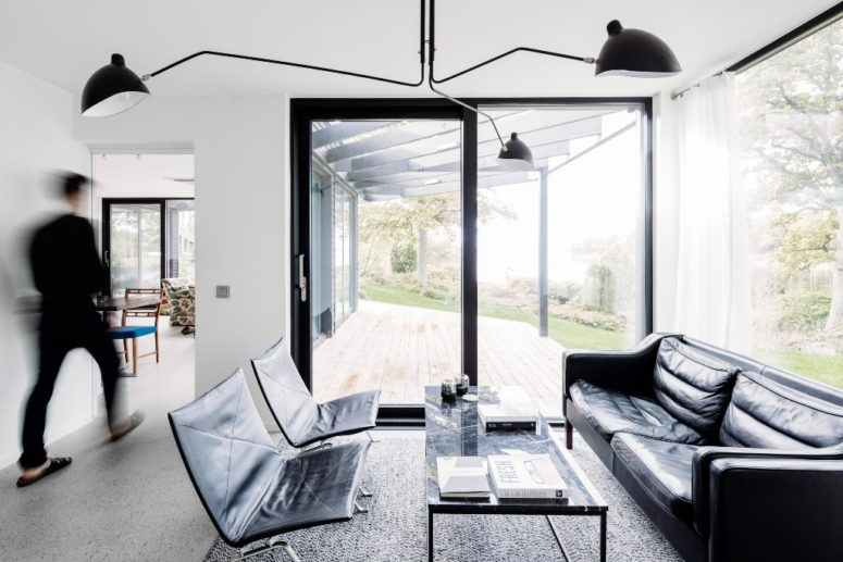 The living room is done in black and white, with modern and minimalist furniture and much glazing