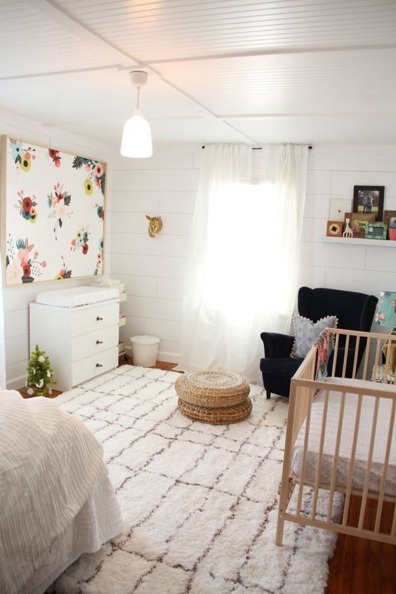 a boho master bedroom with a crib, a comfy chair with a footrest and a changing table in the corner