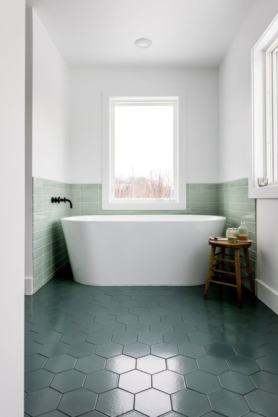 a contemporary bathroom with a bathtub niche covered with green tiles that match dark green floors