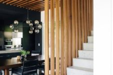 05 a dining space wraped in a vertical wooden plank screen on one side and from above that makes it a design feature