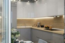 05 a glossy minimalist kitchen with built-in lights and a light-colored wood backsplash for a unique look