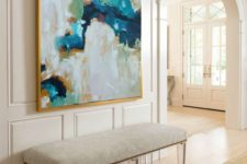 05 a modern bench with acrylic legs, creamy upholstery and an abstract artwork with creamy shades