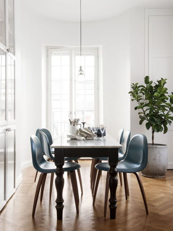 a vintage black and white table and mid-century modern blue chairs on curved legs to a bold look