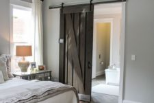 05 a vintage-inspired farmhouse bedroom with a dark stained sliding barn door to stand out