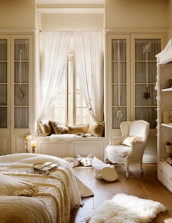 a warm and refined French country chic bedroom with a window seat
