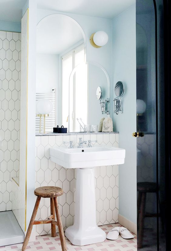 an accent and a task light with layered mirrors in a modern art deco bathroom