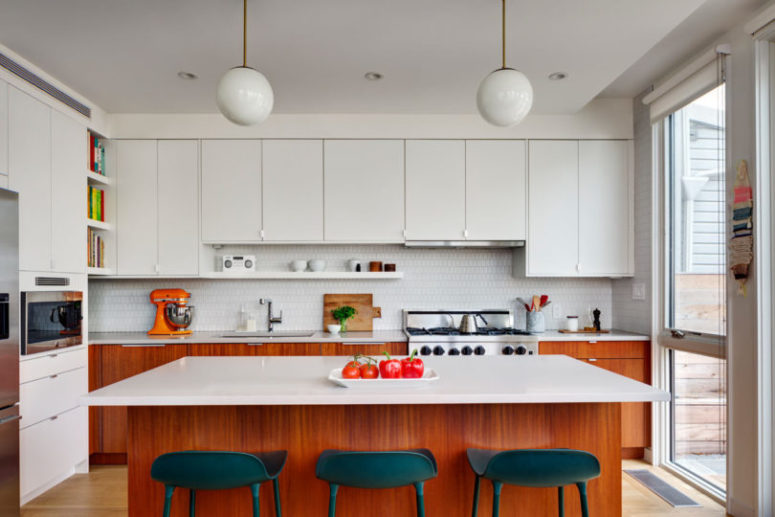 The kitchen si done with white upper and stained wooden cabinets plus a comfy kitchen island