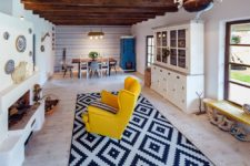 There's a large hearth with a wall plate display and a colorful chair in front of it