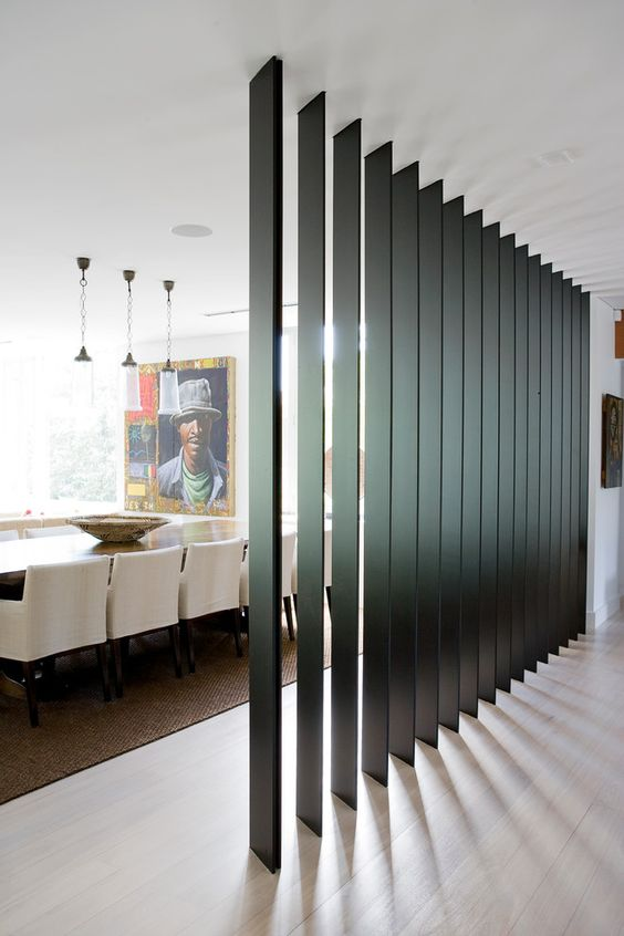 a black wooden plank screen separates the dining room from the entryway and doesn't look bulky