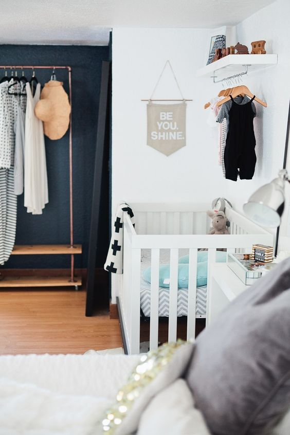 a chic master bedroom with an open closet and a baby's nook with a crib and a hanging closet over it