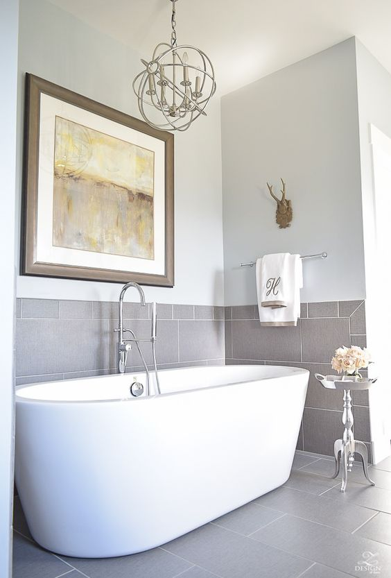 a cozy and elegant bathroom niche done with grey tiles and a modern free-standing tub